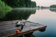 Angelrute, spinnende Spule auf der Hintergrundpierflussbank SU lizenzfreie stockfotografie
