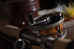 Angelrute und Spule der Fliege mit ledernem Fall und Feder fliegt lizenzfreies stockfoto