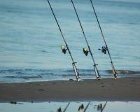 Angelruten auf dem Seeufer Stockfotos