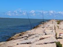 Angelruten auf den Anlegestellen, die im Fluss fischen Stockfoto