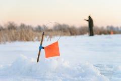 Angelruten- und Eislochabschluß des Winters oben, Kipp mit Spule und orange Flaggengerät Lizenzfreies Stockfoto