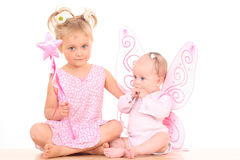 Angels. 6 months little baby girl with pink wings and her sister Stock Photo