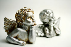 Angels. Busts of two little angles watching something, supporting their heads with their hands; golden and silver - worn; light background Royalty Free Stock Photos