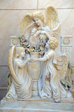Angels. A white statue of one adult angel and two child angels against a marble block wall stock photos