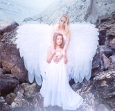 Angels on the beach. Angels. Mom and daughter with white wings Royalty Free Stock Photo