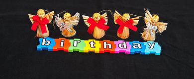 Angels and birthday. Text  birthday  in white letters on colorful jigsaw style colorful pieces  with angels above isolated on black background with space for Stock Image