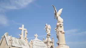 Angels and crosses on grave monuments in cemetery. Action. White stone sculptures and crosses tower on background of