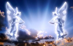 Angels with divine Light. Two angels over beautiful sky with divine rays of light Stock Photo