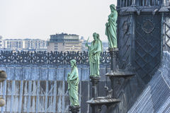 Angels facing gargoyles on top of Notre-dame Cathedral Stock Photo