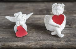 Angels with hearts icons of love and valentine`s day. Two ceramic angels. They have red hearts in their hands Stock Images