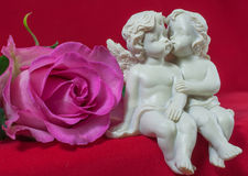 Angels kissing and pink rose Stock Images