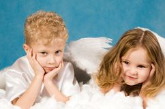 Angels rest. Photo of small boy and girl in angel dresses lying on white cloud and having rest Royalty Free Stock Photo