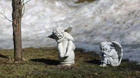 Angels in the spring garden. Statues of angels in the spring garden stock photo
