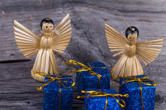 Angels of straw and Christmas Package. Two angels of straw and Christmas Package on wooden background Royalty Free Stock Photo