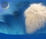 Angels wing with moon and northern lights. Angels feather wing on sky blue background with slight halo blur for effect and moon with northern lights heaven Stock Photo
