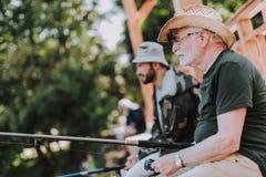 Angenäm äldre man som fiskar samman med hans son fotografering för bildbyråer