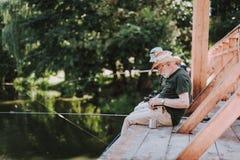 Angenäm åldrig man som sitter på träbron fotografering för bildbyråer