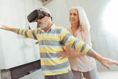 Angenäm åldrig man som testar VR-exponeringsglas med hans älska fru Arkivbild