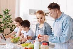 Angenäm familjrestign i köket tillsammans arkivfoton