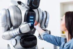 Angenäm flicka som trycker på roboten royaltyfri foto