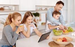 Angenäm full familj som tillsammans spenderar tid i köket arkivbild