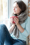 Angenäm gladlynt kvinna som tycker om sikt från fönstret Arkivfoton