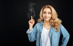 Angenäm gullig kvinna som pekar på raket Royaltyfria Bilder