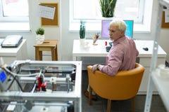 Angenäm hög man observera skrivaren 3D från hans arbetsplats Arkivbilder