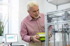Angenäm hög man som kontrollerar kapacitet av skrivaren 3D Arkivfoton