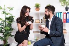 Angenäm konversation för man och för kvinna under kaffeavbrott Diskutera kontorsrykten Fråga för rekommendationer kaffe mer tid arkivbild