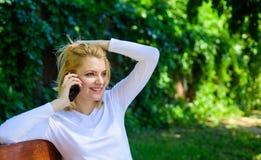 Angenäm konversation Flickablondin som ler bakgrund för natur för gräsplan för framsidasamtalsmartphone Kvinna som har angenämt royaltyfri foto