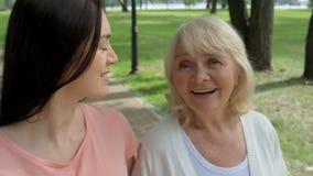 Angenäm kvinna och hennes hög moder som går i parkera