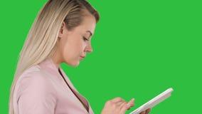 Angenäm kvinna som använder minnestavlan på en grön skärm, Chromatangent arkivfilmer