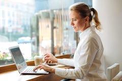 Angenäm kvinna som framkallar app, medan ha kaffe Arkivbild