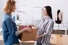 Angenäm kvinna som hjälper hennes kollega att bära en ask Arkivbild