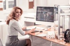Angenäm kvinna som sitter på kontorstabellen arkivfoto