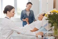 Angenäm kvinnlig doktor som tar en flaska med medicin arkivfoto