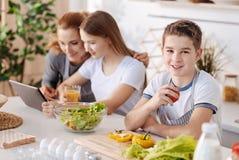 Angenäm le pojke som vilar i köket med hans familj royaltyfria bilder