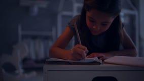 Angenäm liten flicka som gör hennes läxa i hennes sovrum arkivfilmer
