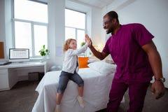 Angenäm liten flicka som ger högt fem till yrkesmässigt pediatriskt royaltyfri foto