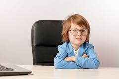 Angenäm ljust rödbrun pojke med skeptikeruttryckt som ser kameran royaltyfria foton