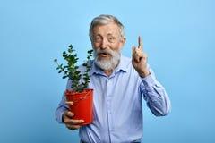Angenäm lycklig man som pekar upp, medan rymma en busket med blomman arkivfoto