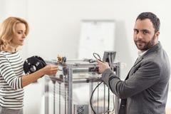 Angenäm man som poserar, medan förbereda skrivaren 3D för arbete Arkivfoto