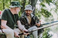 Angenäm man som talar med hans son, medan fiska arkivfoton