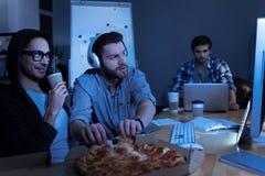 Angenäm positiv programmerare som tar pizzaskivor royaltyfria bilder