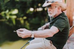 Angenäm skäggig åldrig man som rymmer en metspö royaltyfria foton