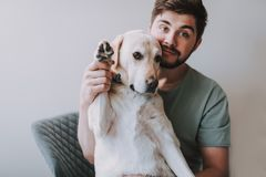 Angenäm skäggig man som sitter med hans hund fotografering för bildbyråer