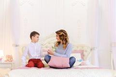 Angenäm skärm av uppmärksamhet från den lilla sonen för mamma i form av Arkivfoto