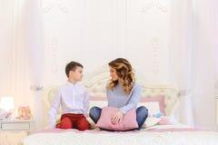Angenäm skärm av uppmärksamhet från den lilla sonen för mamma i form av Arkivfoton