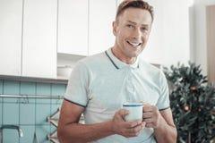 Angenäm stilig man som ler och rymmer en kopp royaltyfri fotografi
